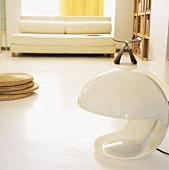 Heller, junger Wohnraum mit Bodenlampe und japanischem Designer Hocker und schlichtem Sofa im Hintergrund