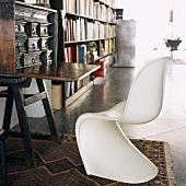Weisser 60er Jahre Kunststoff-Schalenstuhl vor einem antiken Sekretär und Bücherregalen im Hintergrund