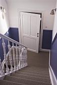 Modern renovierte Landhaus-Treppe mit Sisalbelag und lavendelblau gestrichener, halbhoher Sockelbereich