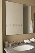 Spiegelung eines Schriftzuges im Badezimmerspiegel über einem Marmorwaschtisch mit Retro-Armatur
