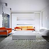 Zeitgenössische Wohnraum-Architektur mit orangefarbenen Designer-Sofas vor grosszügigem Einbauschrank und kubischem Couchtisch