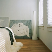 Weisser Schlafraum mit plüschiger Decke auf dem Bett, geschlossenen Jalousien und Akt-Malerei im Hintergrund