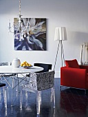 Original mixture of styles - designer chairs with plexiglas legs at round table and tripod standard lamp