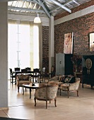 Open-plan living-dining room in loft apartment with period furniture, rough brick walls and exposed roof structure
