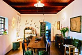 Prettily decorated dining room with rustic table and ruddy wooden ceiling