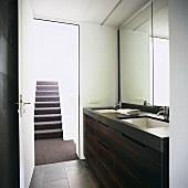 Modern washstand with twin sinks below mirrored wall