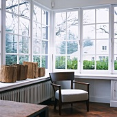 Upholstered wooden chair below conservatory windows with rough chunks of wood on windowsill