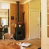 Wood-clad interior with wood-burner in corner and animal-skin rug