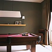 Corner of room with heavy pool table, wooden floating shelf and French doors with curtain