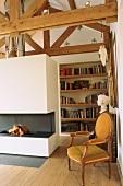 Wohnraum mit offenem Dachstuhl, Bücherwand und Kaminfeuer