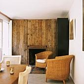 Wohnzimmer mit rustikaler Holzwand und Korbmöbel