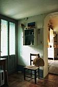 Einfache Diele mit Fenstertür, altem Holzstuhl und Durchgang mit Rundbogen