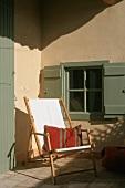 Sonnenbeschienener, kleiner Innenhof mit weißem Liegestuhl und Ethnokissen