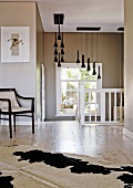 Chair and cowhide rug on landing