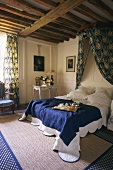 Bedroom with wood-beamed ceiling, canopy, rug and blue and white bedspread with breakfast tray on bed