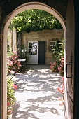 View through archway of sunny courtyard with shady, vine-covered pergola and abundant flowers
