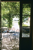 View of garden terrace with shady pergola, delicate metal furniture, carafe of wine and wine glasses