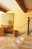 Stairwell with stone flags, stone steps, large oil painting on the wall and rustic, round wooden ceiling beams