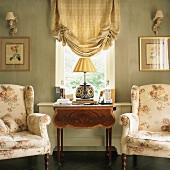 Elegante Sessel mit floralem Muster; dazwischen ein antiker Beistelltisch unter einem Fenster mit kariertem Raffrollo
