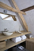 Washstand made from thick wooden boards and long narrow mirror under sloping attic ceiling with exposed beams