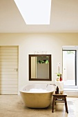 Free-standing bathtub and square framed mirror next to toiletries on simple wooden stool