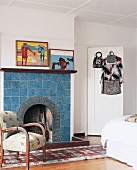 Open fireplace with blue-tiled surround, rug, armchair and modern pictures on wall