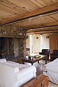 Herrschaftlicher Wohnraum mit großem, gemauertem Natursteinkamin, weissen Sofas und Ledersesseln unter einer niederen Holzdecke mit runden Balken