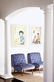 View through archway with Doric columns of two easy chairs with blue patterned upholstery below Chinese prints