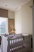 Nursery with white cot and view of tree