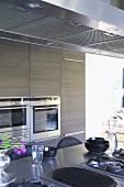 Blick vom Küchenblock mit Edelstahlarbeitsfläche auf eingebaute Küchengeräte