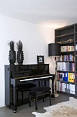 Black glossy piano and bookcase in corner of room