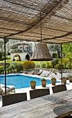 Terrasse mit luftigem Sonnenschutz, Korblampe, Esstisch und mit Swimming Pool im Hintergrund