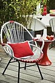 Rot-weisser Gartenstuhl im Fifties-Stil mit Kissen, auf einer Holzterrasse stehend