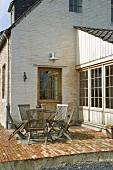 Backsteinhaus mit gepflasterter Sonnenterrasse; darauf einen runde Metalltisch und Klappstühle aus Holz