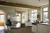 Helle Landhausküche mit Küchenblock, Fenstertüren, Sprossenfenstern, Holzschränken und Küchengeräte mit Edelstahlfront