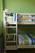 Einfaches Holz-Etagenbett mit farbenfroher Bettwäsche und lustigem Stoffhasen im Kinderzimmer