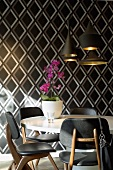 Dining table and chairs in front of sober, geometric wallpaper with purple orchid lightening the atmosphere
