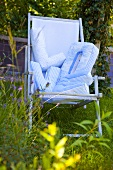 Blue deck chair in a garden with pillows which spell 'LOVE'
