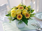 Vase of yellow flowers on laid table