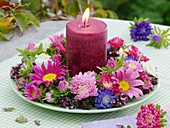 Candle in wreath of asters and oregano on plate