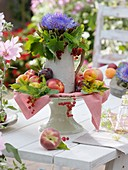 Artichoke flower with redcurrants and stone fruit on cake stand