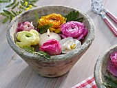 Ranunculus flowers, narcissus and floating candle in bowl