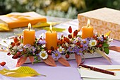 Autumnal arrangement of flowers, rose hips and candles on table