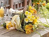 Gelber Blumenstrauss aus Herbstchrysanthemen und Chinaschilf