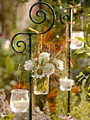 Flowers and candles in jars hanging on an ornamental post