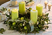 Advent wreath of mistletoe and spruce with green candles