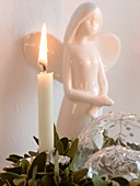 White candle in front of porcelain angel