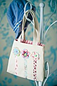 Girl's bag with floral motifs hanging on metal coat stand
