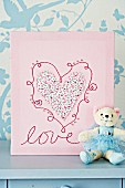 Handmade picture with heart & embroidery behind teddy bear dressed as ballerina
