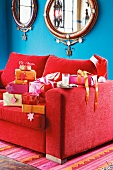 Christmas gifts on a red sofa
